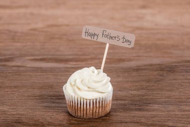 tasty cupcake with Happy fathers day inscription on wooden surface