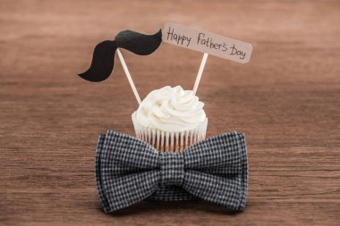 tasty cupcake with mustache sign, bowtie and Happy fathers day inscription on wooden surface