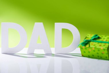 green gift box near dad inscription made of white letters on green, Happy fathers day concept