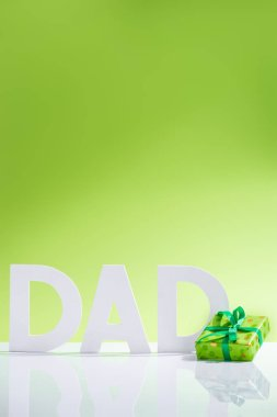 green gift box in front of dad inscription made of white letters on green, Happy fathers day concept