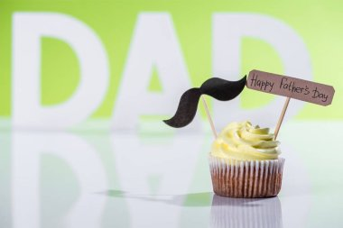 creamy cupcake with mustache sign and Happy fathers day inscription in front of dad inscription made of white letters on green
