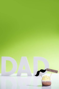 cupcake with mustache sign and Happy fathers day inscription in front of dad inscription made of white letters on green
