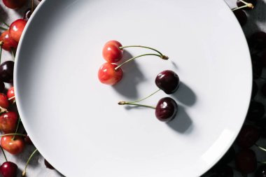 top view of ripe red and yellow cherries on white plate