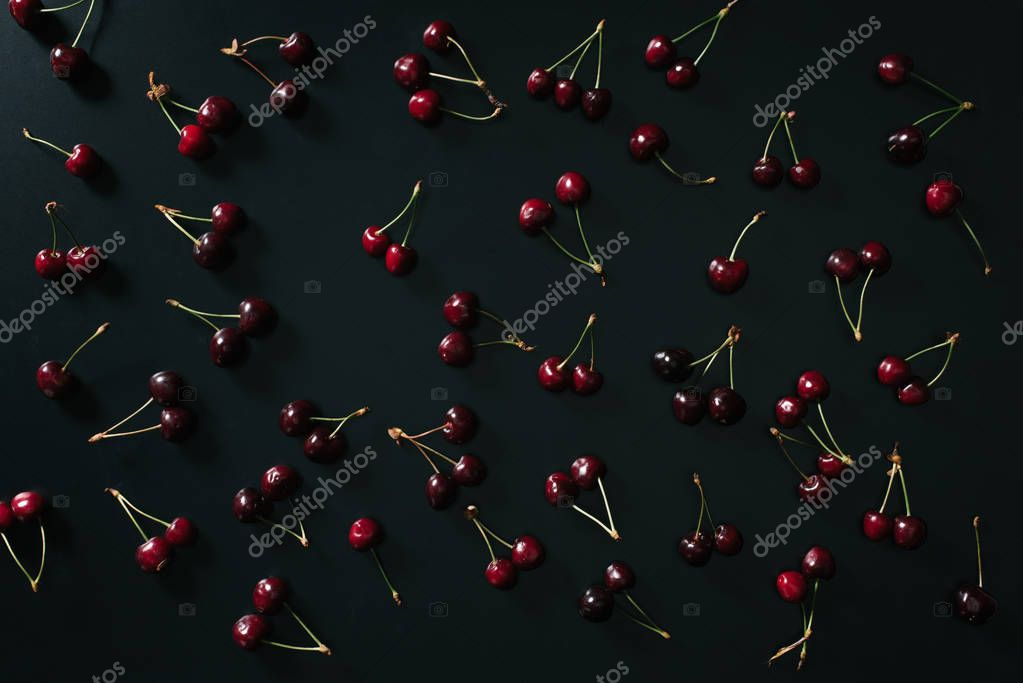top view of fresh ripe red sweet cherries on black background