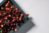 top view of fresh ripe sweet cherries in wooden box on white