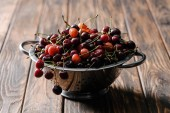 colander with fresh ripe sweet cherries on rustic wooden table