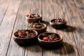 Fotografie čerstvé zralé třešně v miskách na dřevěný stůl