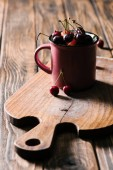 Fotografie healthy tasty cherries in pink cup on wooden cutting board on table