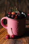 Fotografie close-up view of fresh ripe cherries in wet pink cup on wooden table