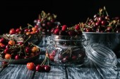 Fotografie ripe sweet cherries in glass jar and colander on wooden table