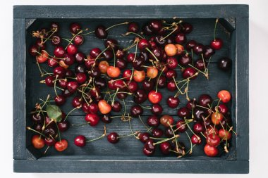 top view of fresh ripe sweet cherries in wooden box isolated on white