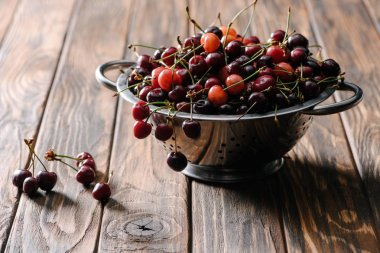 colander with fresh sweet healthy cherries on rustic wooden table
