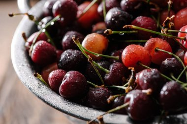 close-up view of fresh sweet organic cherries with water drops in colander