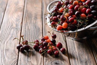 colander with fresh ripe sweet cherries on wooden table