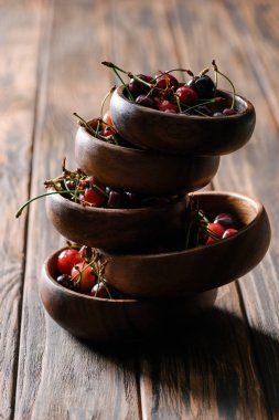 stacked bowls with fresh ripe cherries on wooden table