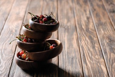 tower made from bowls with fresh ripe cherries on wooden table