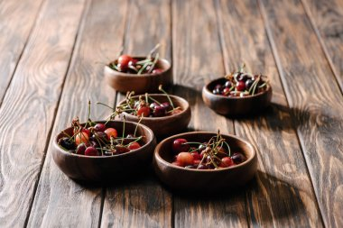 fresh ripe sweet cherries in bowls on wooden table