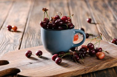 close-up view of ripe fresh sweet cherries in blue cup on wooden cutting board on table