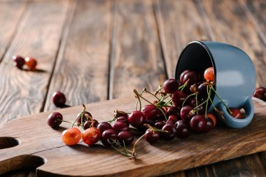 close-up view of organic sweet cherries in blue cup on wooden cutting board on table
