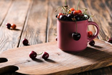 close-up view of organic sweet cherries in pink cup on wooden cutting board on table