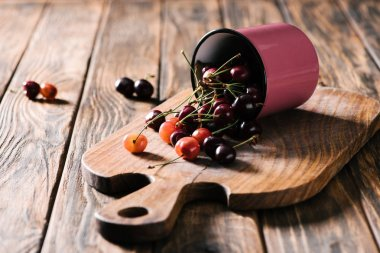 ripe fresh sweet cherries in pink cup on wooden cutting board on table