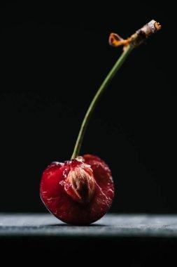 close-up view of half of fresh ripe cherry on black
