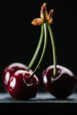 close-up view of ripe organic cherries with water drops on black