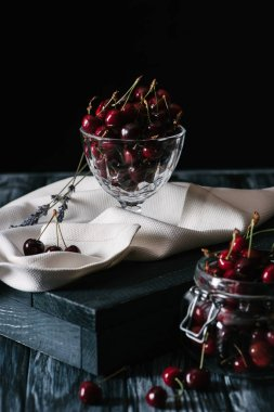 close-up view of fresh ripe sweet cherries in glass utensils on wooden table