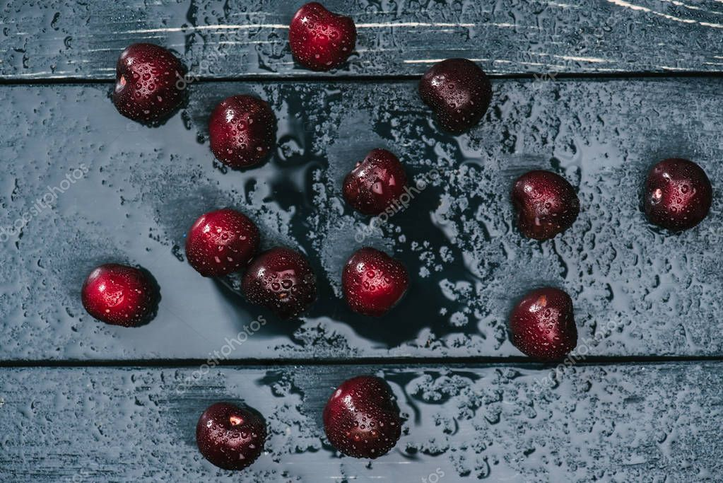 top view of fresh ripe sweet cherries on wet wooden surface