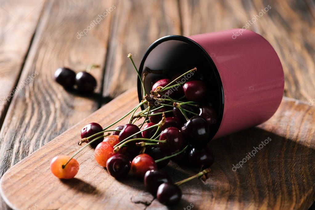 close-up view of ripe fresh sweet cherries in pink cup on wooden cutting board on table
