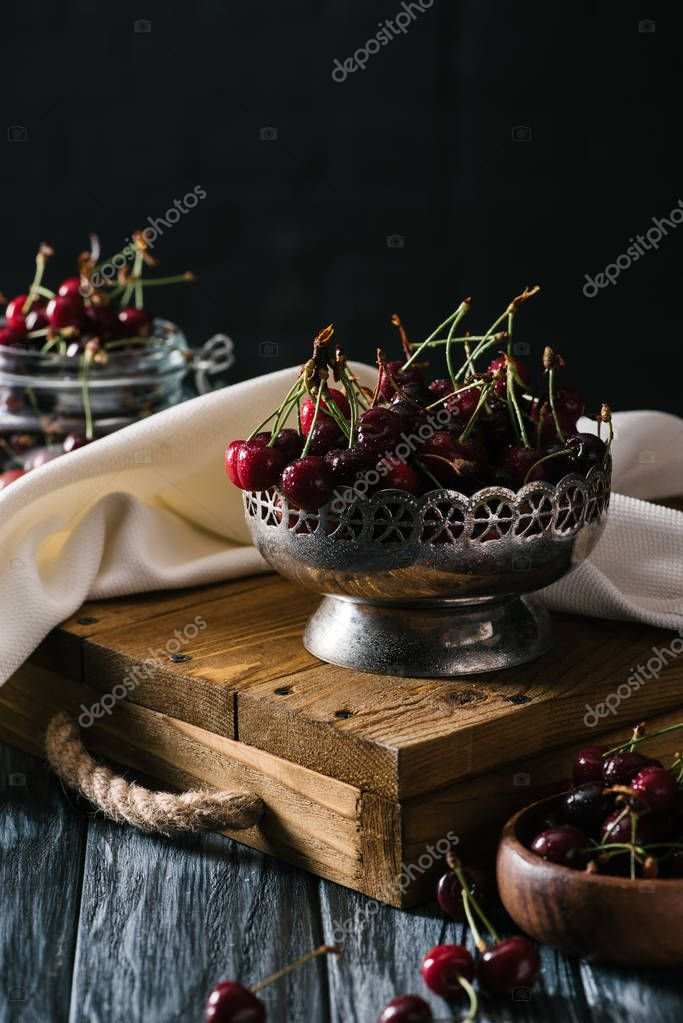close-up view of ripe fresh cherries in vintage bowl on wooden table