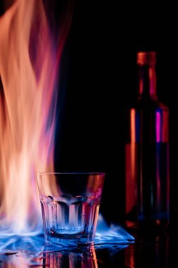 close up view of flame, empty glass and bottle of sambuca alcohol drink on black background