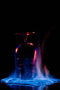 Close up view of glasses and burning sanbuca alcohol drink around on black background stock vector