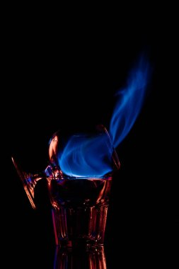 close up view of alcohol sambuca drink burning in glass on black background