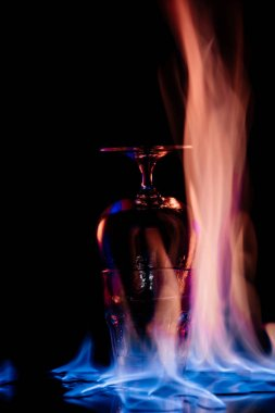 close up view of alcohol sambuca drink in glass and flame on black background