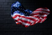 Photo dynamic waving united states flag in front of black brick wall, Independence Day concept