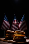 tasty burgers on wooden cutting board in front of small united states flags