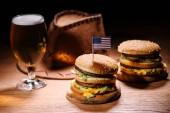 chutné hamburgery na dřevěný stůl s americký kovbojský klobouk a studené sklenice piva