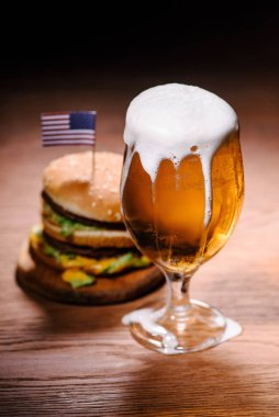 Tasty burger with glass of beer on wooden table stock vector