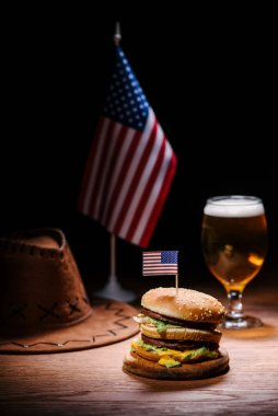 Delicious burger on wooden table with american cowboy hat, usa flag and glass of beer stock vector