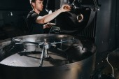 Fotografie Man adjusting handle of machine for professional coffee production