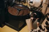 Fotografia Sacchetto di carta di riempimento di uomo con chicchi di caffè appena tostati