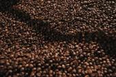 Datailní pohled zrnkové kávy pražené v profesionální stroje