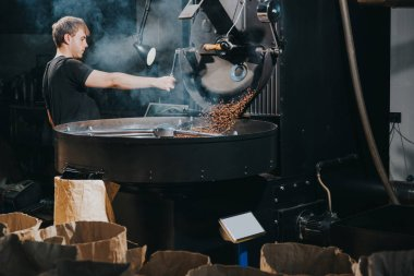 Man controlling process of roasting coffee beans in traditional machine