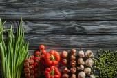 Draufsicht auf verschiedene rohe Gemüsesorten auf Holztischplatte