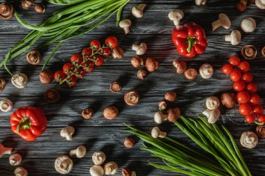top view of various raw vegetables and mushrooms on wooden tabletop