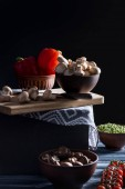 Fotografia funghi champignon e verdure diverse sul tavolo sul nero