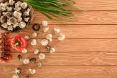 Draufsicht auf Champignon-Pilze und verschiedene Gemüsesorten auf hölzerner Tischplatte