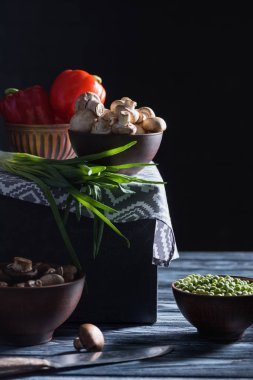 raw champignon mushrooms and different vegetables on table on black