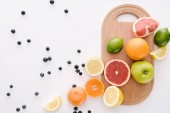 Fotografie top view of citrus fruits with blueberries and wooden cutting board on white surface